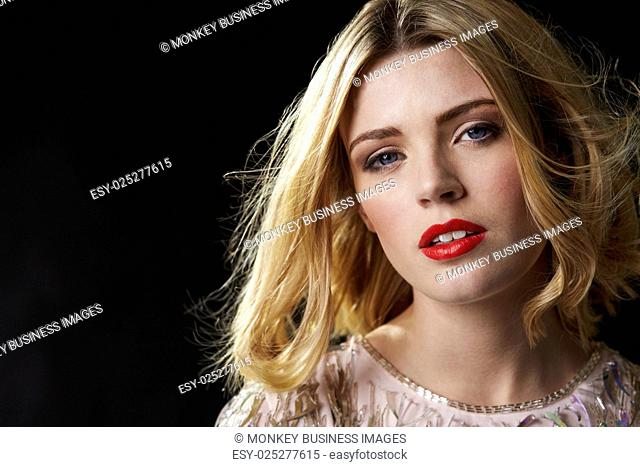 Glamorous blonde woman with hair blowing, close up portrait