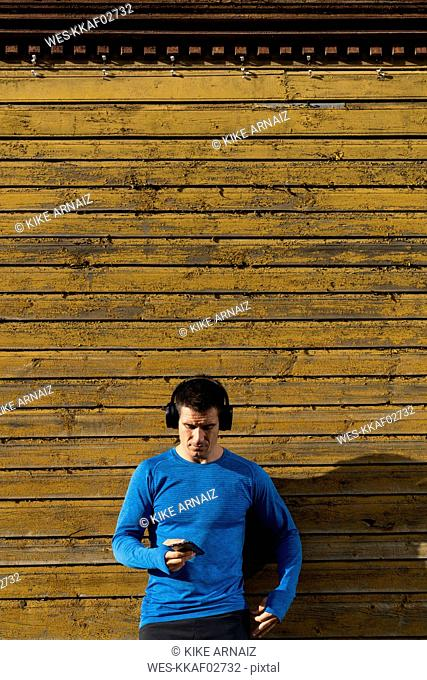 Athlete leaning against house wall with cell phone and headphones