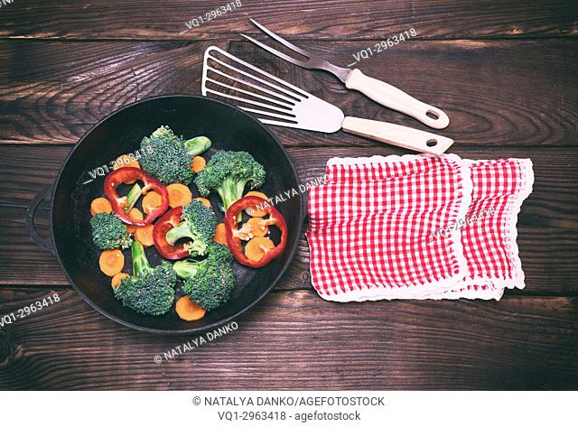 black cast-iron frying pan with pieces of carrots, broccoli and peppers on a brown wooden background, top view