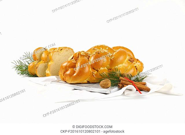 loaf of Christmas sweet braided bread on wooden cutting board and white napkin