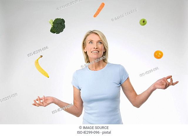 A woman juggling fruit and vegetables