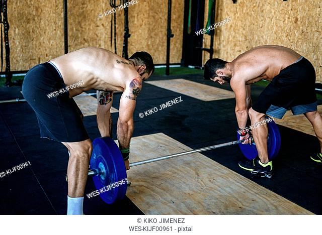 Two athletes preparing barbell in gym