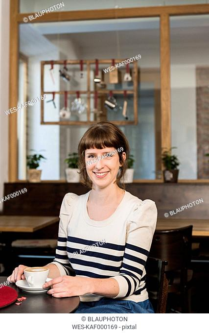 Portrait of smiling woman sitting in a cafe with cup of coffee