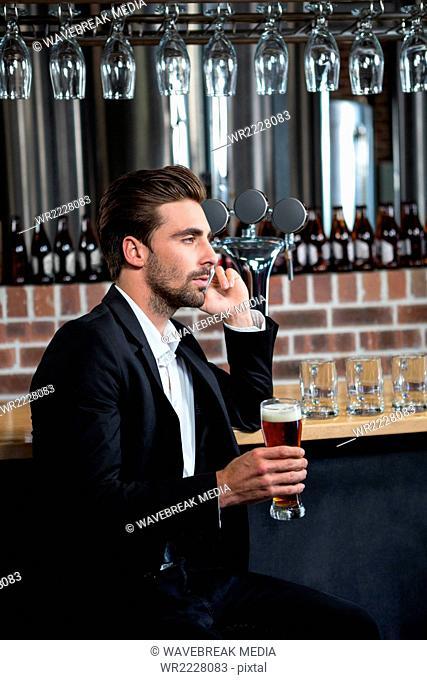 Handsome businessman holding a pint