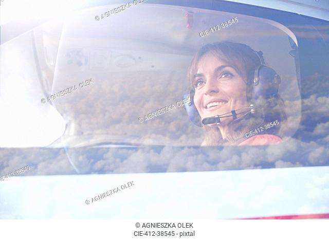 Smiling female pilot flying airplane in cockpit