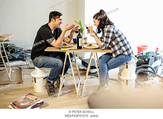 Happy couple renovating flat, taking a break, eating pizza