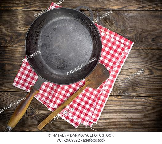 empty black round frying pan with a wooden handle on a brown background, top view