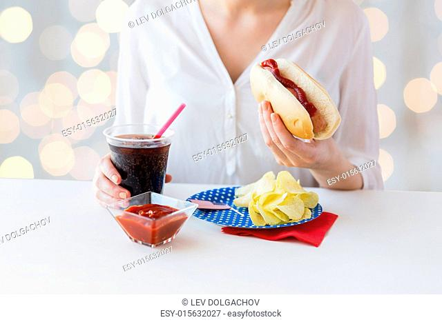 american independence day, celebration, patriotism and holidays concept - close up of woman hands holding hot dog and cola in plastic cup with potato chips and...
