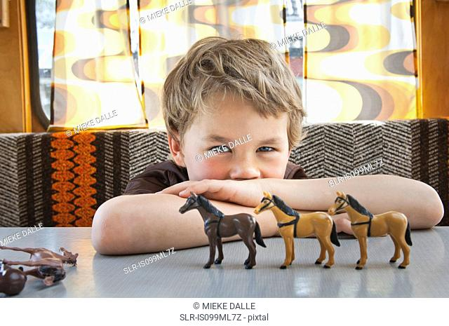 Boy playing with toy plastic horse in caravan
