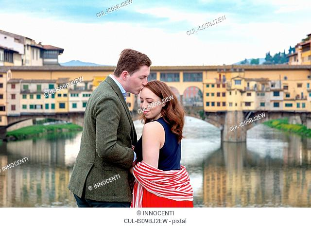 Young man kissing woman, Ponte Vecchio, the Old Bridge, Florence, Toscana, Italy