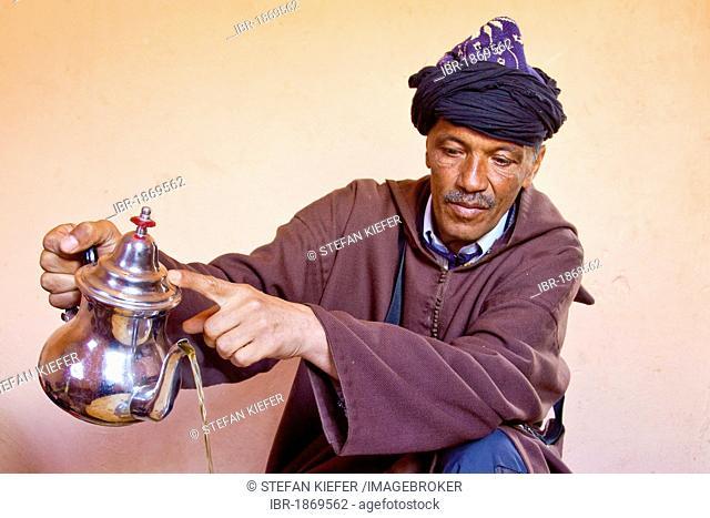 Berber wearing a Djellaba, a traditional robe, pouring mint tea, High Atlas Mountains near Asni, Morocco, Africa