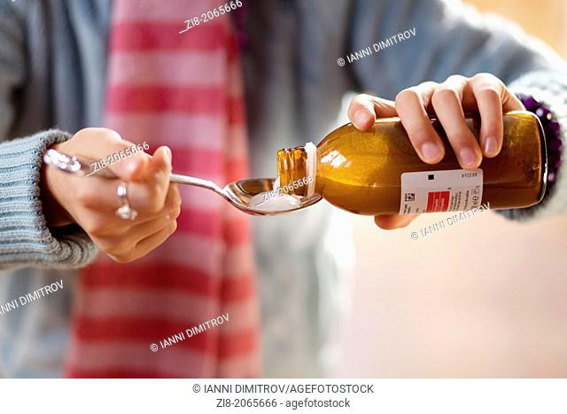 Child pouring cough medicine -close-up