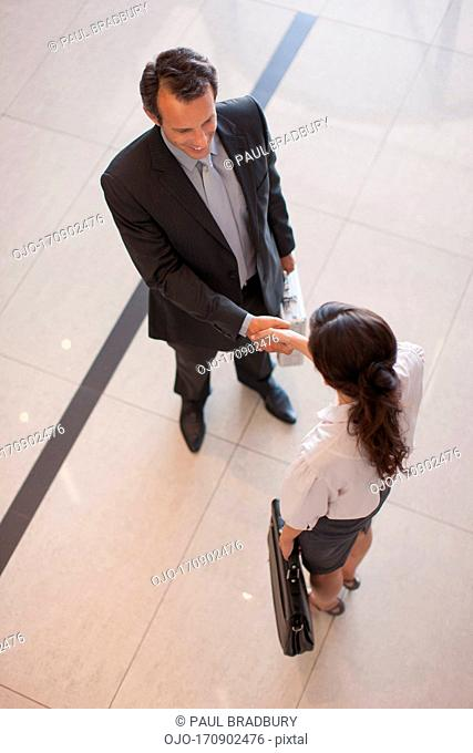 Business people shaking hand in lobby