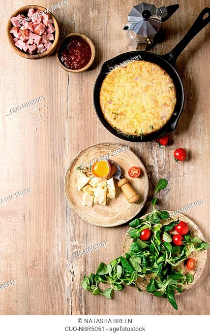 Spanish potato omelette tortilla with bacon served in cast-iron pan with sauce and ingredients above over wooden background. Top view, space