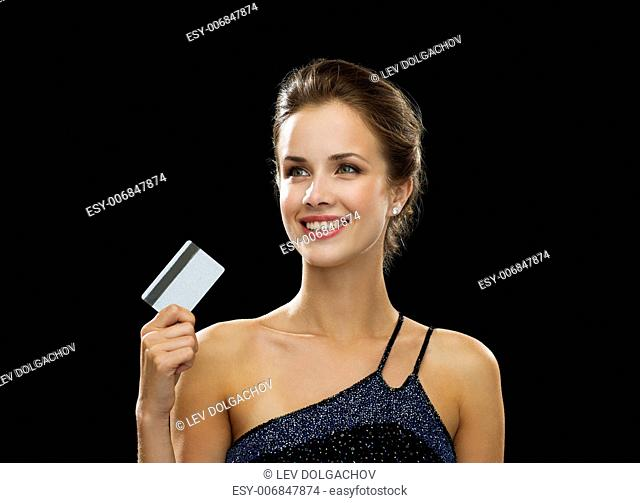 wealth, money, luxury and people concept - smiling woman in evening dress holding credit card over black background