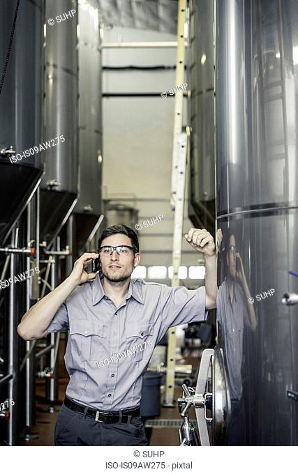 Young man in brewery leaning against storage tank making telephone call