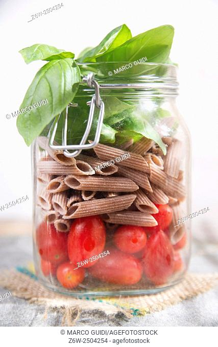 Glass jar with ingredients for pasta with tomato and basil