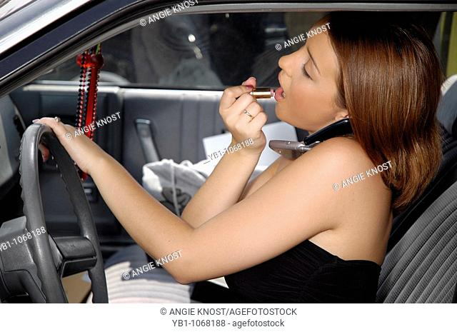 Young woman driving with distractions of phone and make up