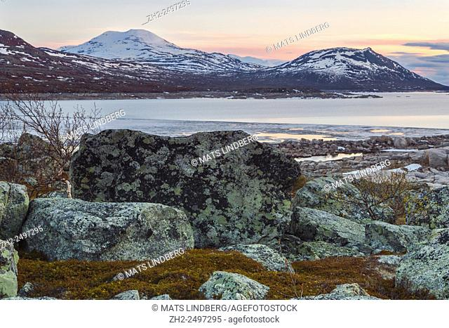 View over Stora lule vatten with mountains with string of snow on them, sunset and the light is reflecting in the water, big rock in foreground