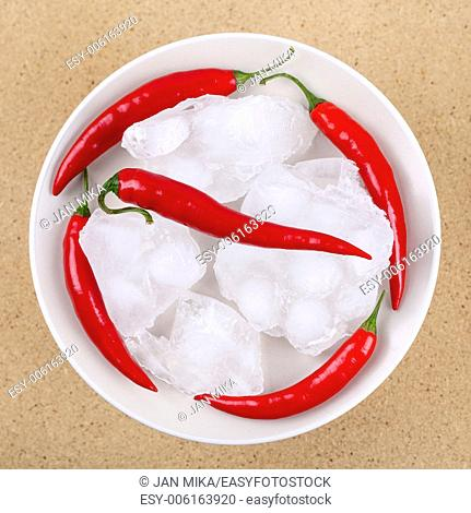 Fresh red hot chili peppers with ice on plate, over wooden background