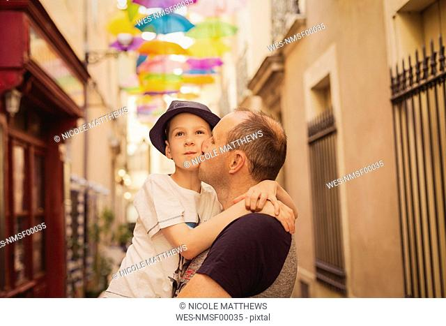 France, Languedoc, Beziers, father kissing son with colorful umbrellas in background