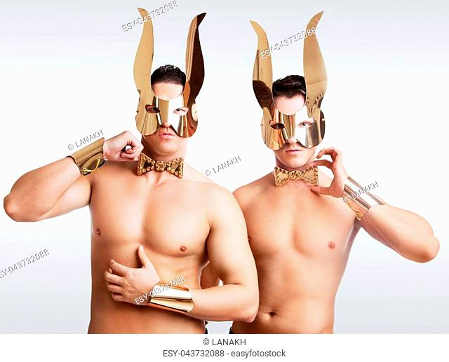striptease dancers wearing golden rabbit ears in the studio isolated against white background