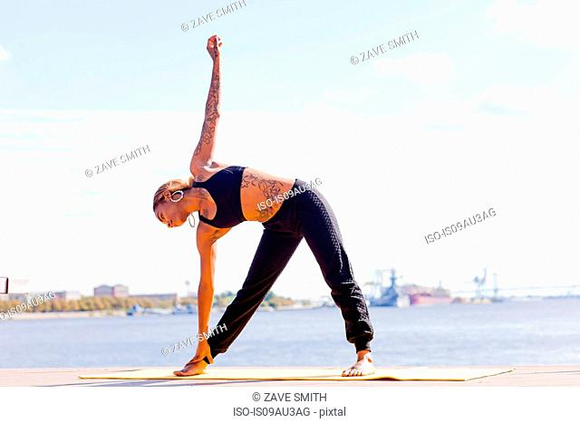 Full length front view of young woman by water in yoga position, Philadelphia, Pennsylvania, USA