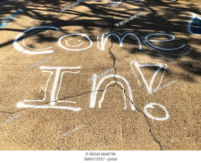 Come In graffitied on the sidewalk