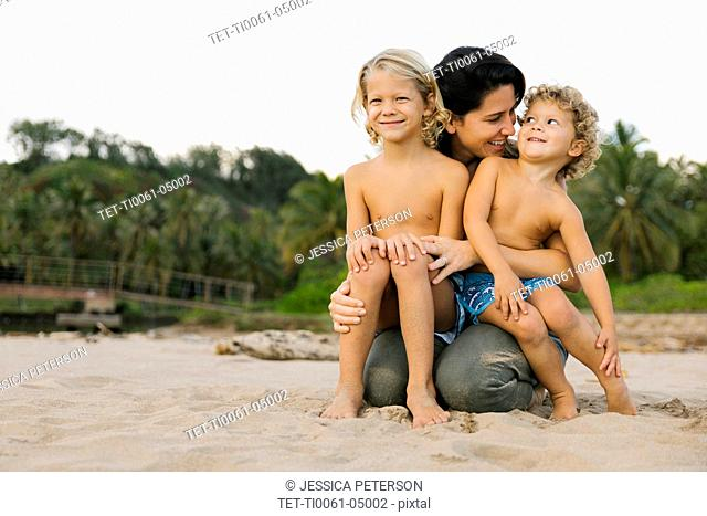 Woman with her sons sitting on her lap on beach