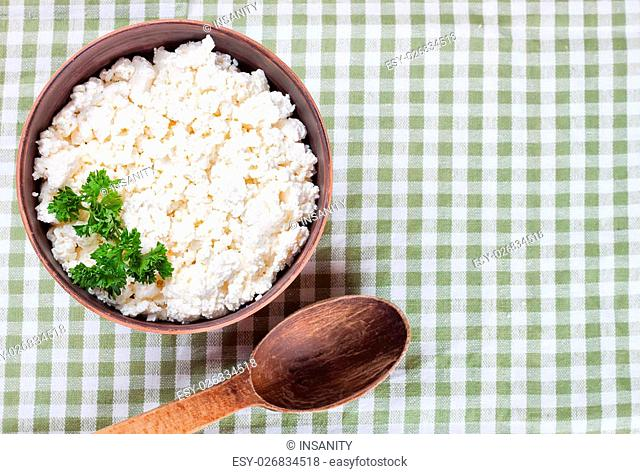 bowl with fresh cottage cheese and wooden spoon on checkered tablecloth background. top view