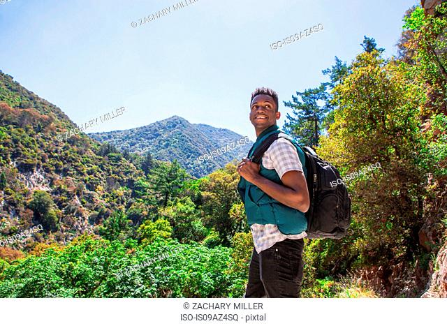 Young male hiker looking over his shoulder in landscape, Arcadia, California, USA