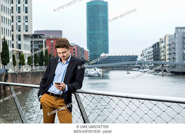 Germany, Hesse, Frankfurt, young businessman standing on a bridge using his smartphone
