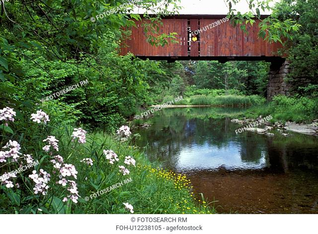 Vermont, covered bridge, Slaughter House Covered Bridge reflects in the water of Dog River in Northfield. A woman looks out over the water from the window of...