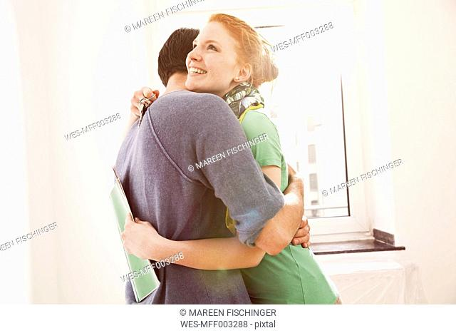 Happy young couple hugging at the window