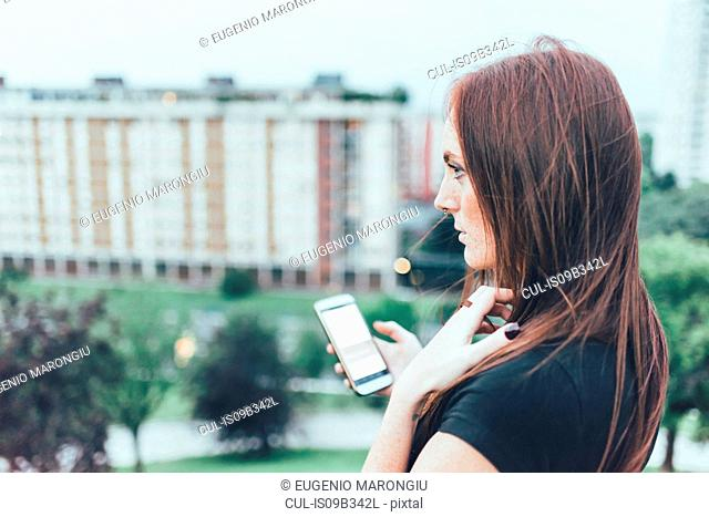 Young woman with long red hair holding smartphone and gazing above city