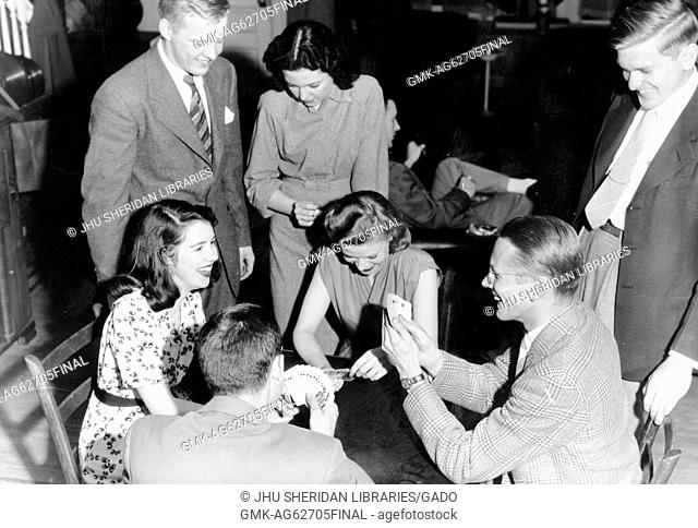 Alpha Delta Phi, Fraternities, Student Life Candid shot of fraternity members and their girlfriends laughing and playing cards, 1947