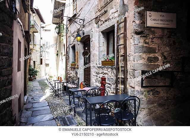 Alley with restaurant tables, Orta, Lake Orta, Piedmont, Italy