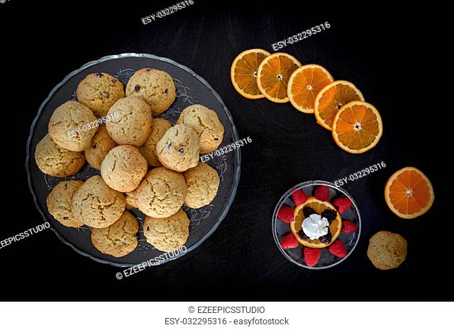 Orange chocolate chips cookies on cake stand besides orange slices and bowl with berries and whipped cream. Top view shot