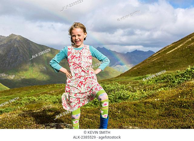 Young girl standing on a hillside at Hatcher Pass, Talkeetna Mountains and rainbow in the background, Hatcher Pass, Southcentral Alaska, USA