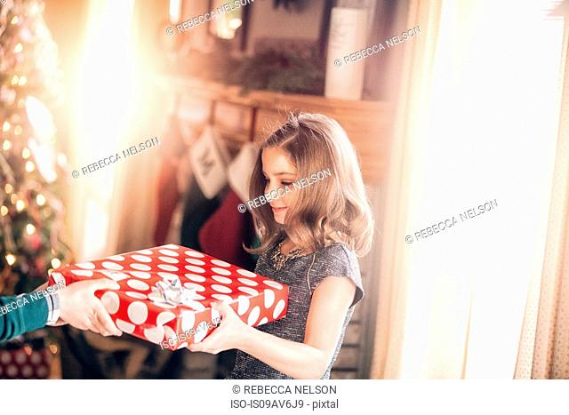 Side view of girl receiving gift at christmas looking down smiling