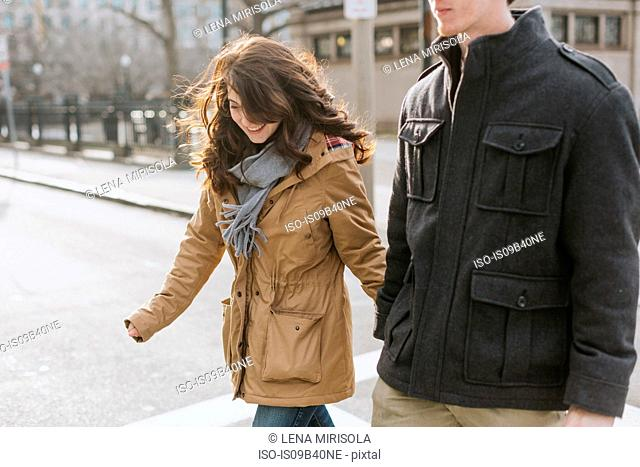 Young couple crossing road, mid section