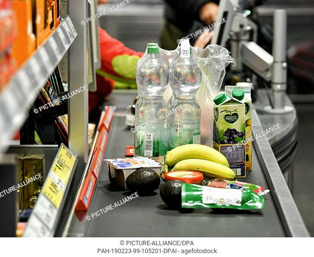 22 February 2019, Berlin: Foods like bananas, water, juice, avocados are lying on the tape at a cash register in the food discounter Penny in Boxhagener Straße