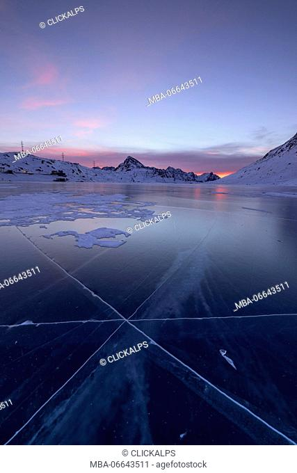 The frozen Lago Bianco framed by the first lights of dawn Bernina Pass canton of Graubünden Engadine Switzerland Europe