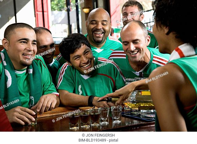 Happy men drinking shots in sports bar