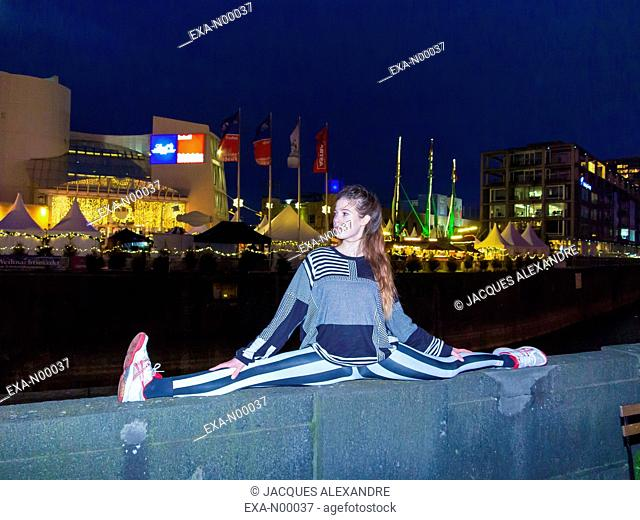 woman doing urban yoga exercises at night on a bridge with an illuminated fair in the background