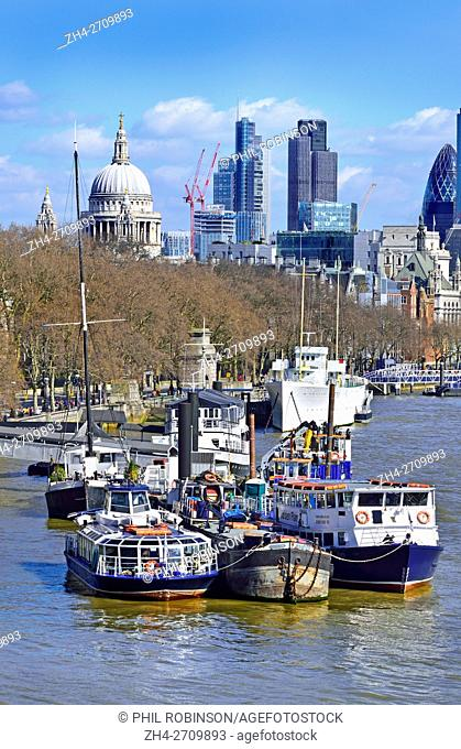 London, England, UK. Boats moored on the River Thames with the City and St Paul's Cathedral in the background