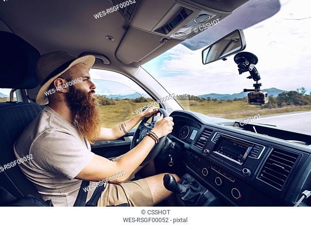 Norway, Lofoten, bearded man driving