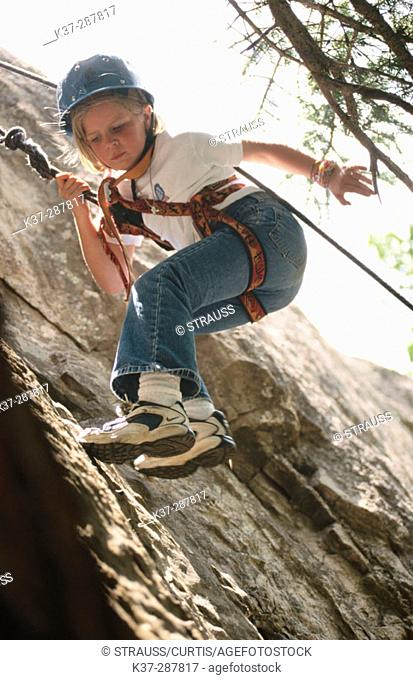 Young girl climbing rock face at rock climbing school. Telluride. Colorado. USA