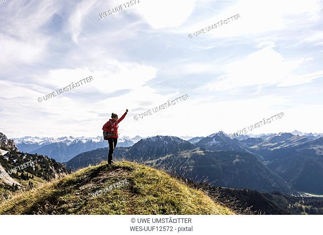 Austria, Tyrol, young woman standing in mountainscape cheering