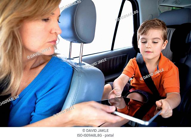 Mother passing digital tablet to son in back seat of car